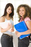 Best friends. Two young woman standing near window and holding notebooks. Looking at camera Stock Photos