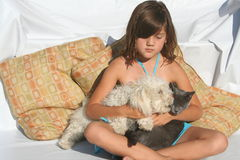 Best Friends. Youing girl sitting with a playful kitten and puppy Stock Image