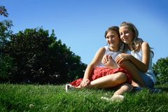 Best friends. Two girls best friends sit in a grass in a park Royalty Free Stock Photo