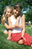Best friends. Two girls best friends sit on grass in a park Royalty Free Stock Photo