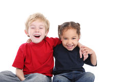 Best friends. Two smiling laughing young children sit with their arms around each other Stock Image
