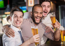 Best friends in a bar. Men shout and rejoice in meeting and drin Royalty Free Stock Photo