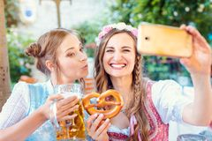 Best friends in Bavarian Tracht making a Selfie with the phone royalty free stock photography