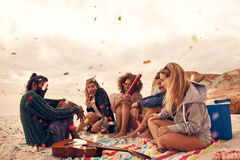 Best friends at beach party. Happy friends partying on the beach with drinks and confetti. Happy young people having fun at beach party, celebrating with Stock Photography