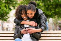 Best friends chatting with smartphone on park bench Royalty Free Stock Photos