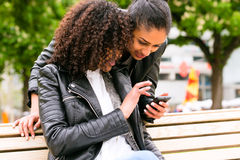 Best friends chatting with smartphone on park bench Stock Photo