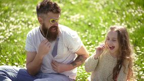 Best friends concept. Dad and daughter sits on grass at grassplot, green background. Family spend leisure outdoors. Child and father posing with glases, bow stock video