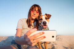 Best friends concept: human taking a selfie with dog. Young female makes self portrait with her puppy outdoors on a beach stock image