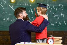 Best friends concept. Teacher with beard, father hugs little son in classroom while discussing, chalkboard on background. Child in graduate cap listening stock image