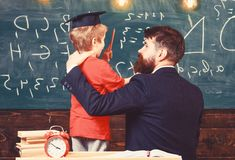Best friends concept. Teacher with beard, father hugs little son in classroom while discussing, chalkboard on background. Child in graduate cap listening royalty free stock images