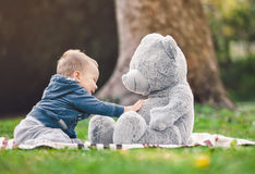 Best of friends. Cute toddler playing outdoors with his teddy bear. Best of friends. Sweet little toddler playing outdoors with his teddy bear Stock Photos
