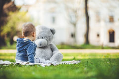 Best of friends. Cute toddler playing outdoors with his teddy bear Royalty Free Stock Photography