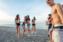 Friends dance on beach under sunset sunlight, having fun, happy, enjoy stock photo