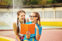 Best friends discuss the diary in park. Best friends discuss the diary in a summer park. Teen girl dressed in shorts and a shirt. On summer vacation. The Stock Images