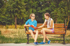 Best friends are discussing book sitting on bench. Royalty Free Stock Photo