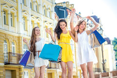 Best friends do shopping. Girls holding shopping bags and walk a Royalty Free Stock Photos