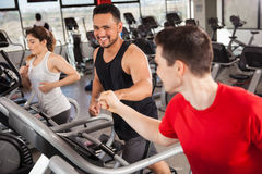 Best friends doing cardio in a gym. Happy young men bumping their fists while doing some jogging on a treadmill at the gym Stock Photo
