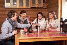 Best friends drinking hot tea in cosy kitchen at winter cottage Stock Photos