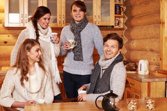 Best friends drinking hot tea in cosy kitchen at winter cottage. Royalty Free Stock Photos