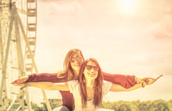 Best friends enjoying time together outdoors at ferris wheel. Concept of freedom and happiness with two girlfriends having fun - Vintage filtered look royalty free stock photos