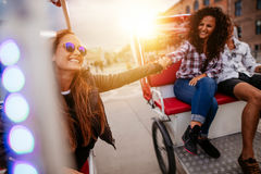 Best friends enjoying tricycle ride in the city Royalty Free Stock Images
