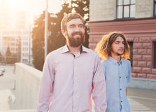 Best friends evening walk. Two men walking in centre of city at sunset, sun flare effect Royalty Free Stock Photography