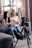 Exuberant female bloggers recording a video stock photo