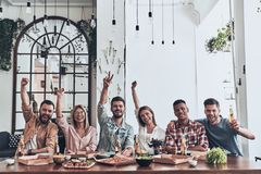 Best friends ever. Beautiful young people in casual wear gesturing and smiling while having a dinner party indoors royalty free stock images