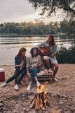 Best friends ever. Group of young people in casual wear smiling while enjoying beach party near the campfire royalty free stock photography