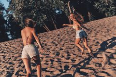 Best friends ever!. Two attractive young women in shorts and swimwear smiling while running on the beach stock images
