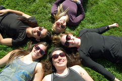 Best Friends. Five girls laying in the grass in a circle royalty free stock photos