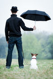 Best friends. Friendship between dog and owner standing in the rain with umbrella Stock Photo