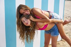 Best friends girls piggyback in summer beach. With blue stripes background Royalty Free Stock Images