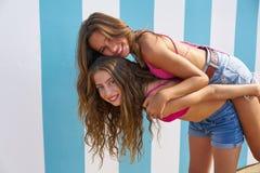 Best friends girls piggyback in summer beach. With blue stripes background Stock Image