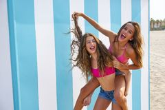 Best friends girls piggyback in summer beach. With blue stripes background Stock Photos
