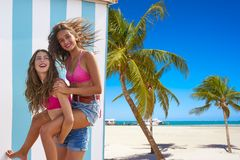 Best friends girls piggyback in summer beach. With blue stripes background Stock Images