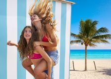 Best friends girls piggyback in summer beach. With blue stripes background Stock Photos