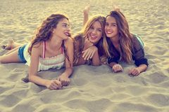 Best friends girls at sunset beach sand. Smiling happy together Royalty Free Stock Photos