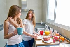 Best friends girls teens breakfast in kitchen Royalty Free Stock Photography