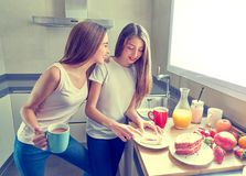 Best friends girls teens breakfast in kitchen Royalty Free Stock Photo