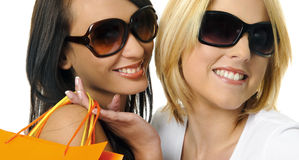 Best friends go shopping. Beautiful blonde and brunette carry their shopping bags together Royalty Free Stock Images