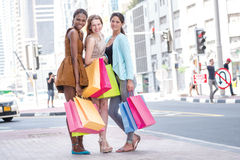 Best friends go to the store. Three girlfriend. Holding shopping bags in their hands while standing on the street among the skyscrapers in downtown and catch a Royalty Free Stock Image
