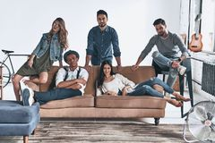 Best friends.  Group of happy young people in casual wear lookin. G at camera and smiling while resting at home Royalty Free Stock Images