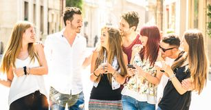 Best friends group having fun together walking on city street - Technology interaction concept in everyday lifestyle with royalty free stock image