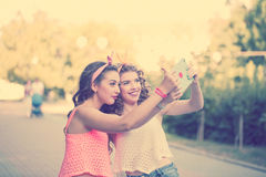 Best friends. Group selfies. Sunset. Best girlfriends do photos. Group selfies. Girls dressed in the style of Pin-up girl. Hipster. Sunset. Warm toning. The Royalty Free Stock Photos
