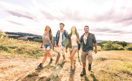 Best friends group walking free on grass meadow - Friendship and freedom concept with young millenial people sharing time royalty free stock photos