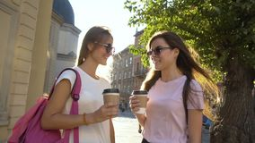 Best Friends Having Coffee in Street. Two pretty caucasian girlfriends in cool sunglasses, with backpacks, are having coffee and talking in the street near old stock video