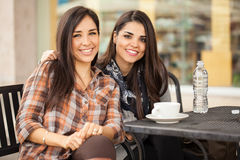 Best friends having coffee together at a restaurant. Portrait of a couple of Hispanic female friends spending some time together and drinking some coffee Royalty Free Stock Images