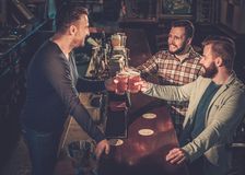 Best friends having fun and drinking draft beer at bar c Stock Photography