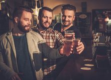 Best friends having fun and drinking draft beer at bar counter in pub. Cheerful old friends having fun and drinking draft beer at bar counter in pub Royalty Free Stock Images